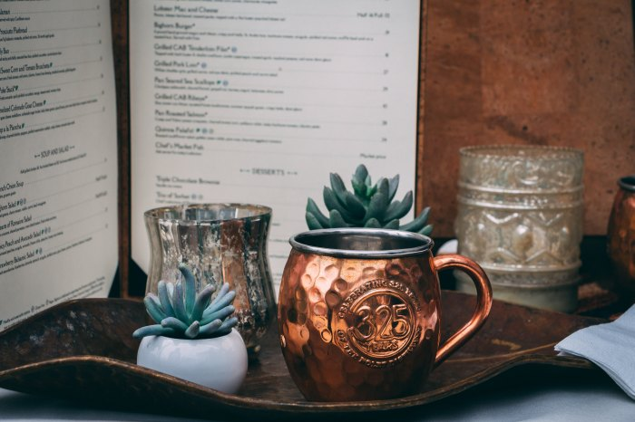 Standing Menu with a cup and plant infront of it.